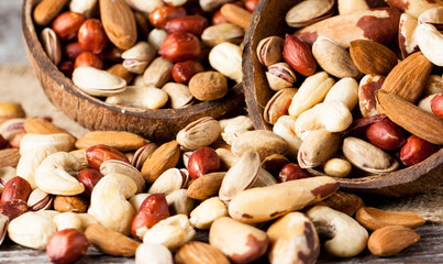 Healthy mix nuts on wooden background. Almonds, hazelnuts, cashews, peanuts, pistachios, brazilian nuts