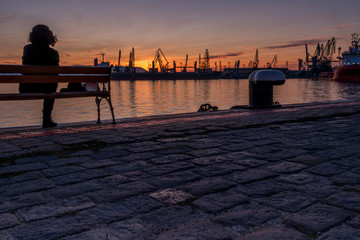 Girl watches the sunset at the sea station with ships.