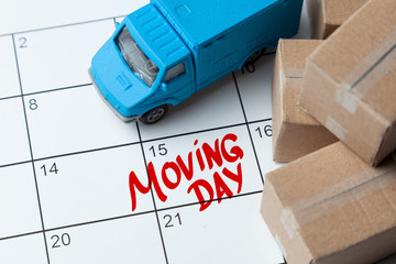 Moving day on the calendar is written in red. Calendar with a note with cardboard boxes and truck.