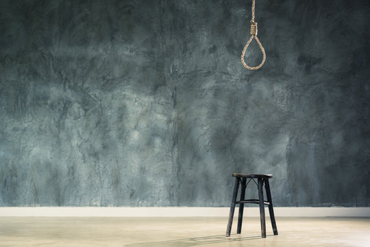 The old chair with the noose hanging at above with space of concrete wall at back, failure or commit suicide concept