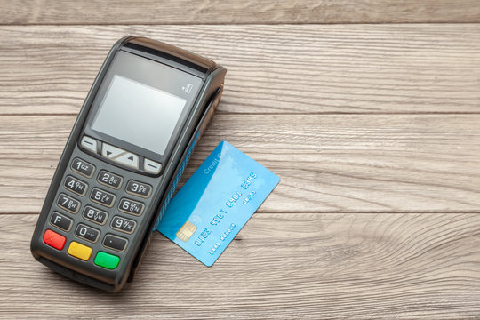 POS terminal, Payment Machine credit card on wooden background. Contactless payment. NFC technology.