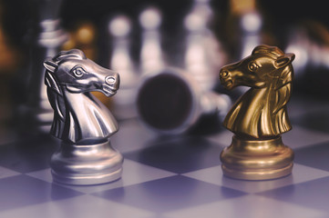 Chess pieces knights facing each other for a standoff. Chess knights confronting each other.