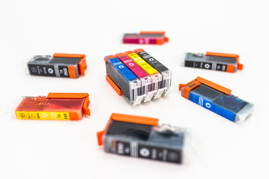 Close-up shot of a CMYK ink cartridges for a color printer isolated on a white background.