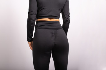 Close up of sportive woman wearing sexy leggings. Rear view of sexual sporty buttocks wearing black tight pants leggings. Copyplace, copy space. Isolated on white background