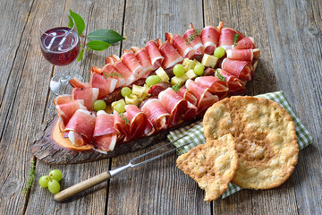 Beim Törggelen in Südtirol: Speck, Kaminwurzen und Bergkäse, dazu Rotwein und Schüttelbrot – South Tyrolean snack with bacon, salami and mountain cheese, served with wine and local crunchy flat bread