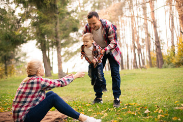 Little cute son playing with parents in forest
