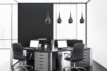 White and black office with laptops