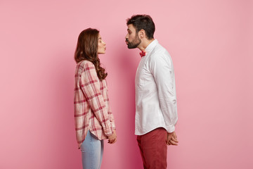 Shot of beautiful couple in love face each other, pout lips and going to kiss, close eyes from pleasure, dressed in stylish clothes, have date, isolated over pink background. Romantic relationships