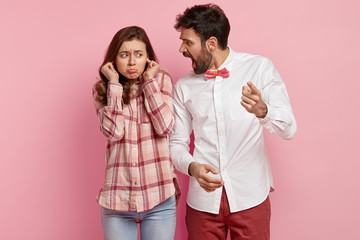 Outraged young man shouts at guilty woman and reproaches about wrong doing, blames, dissatisfied woman plugs ears, ignores loud yelling of angry husband or boss, isolated over pink background.
