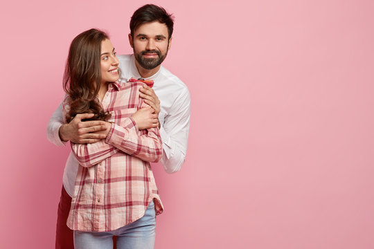 Happy affectionate couple embrace, feel happy, enjoy spending Valentines day together, wear fashionable shirts, express love, stand against pink background with copy space for your promotion