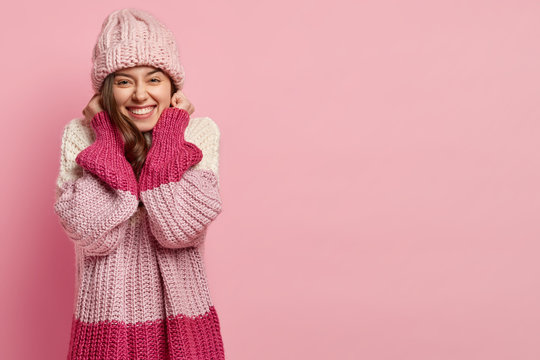 Happy attractive female youngster keeps hand near ears, dressed in warm knitted sweater and headgear, isolated over pink studio background for your advertising content or promotion. Winter season