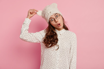 Funny surprised European young woman keeps hand on ear of hat, dressed in polka dot blouse, has folded lips, dark curly hair, isolated over pink background. People, reaction and foolishing concept