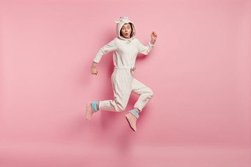 Frightened European young woman in pajams or kigurumi costume, photographed in motion, has fearful expression, isolated over pink background, astonished by shocking news. Morning time concept