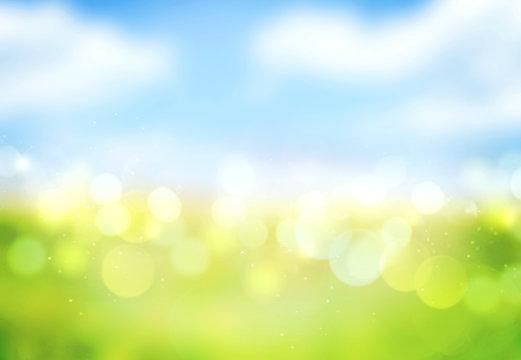 Blue sky green grass blurred bokeh background.