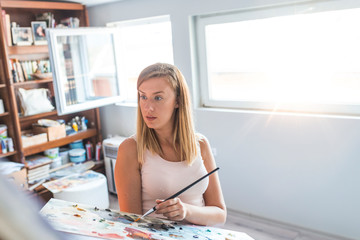 Indoor shot of professional female artist painting on canvas in studio. Woman painter painting in her workshop.