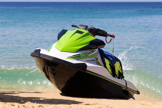 A green-white jet ski is on a beach in waves of blue sea in the sunny weather. Active rest is happy time for all family.
