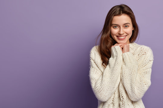 Pleased beautiful lady with toothy gentle smile, has healthy skin, green eyes, long straight hair, holds hands under chin, wears warm white jumper, happy to be photographed, stands over lilac wall