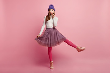 Image of surprised cute woman raises leg, has stupefied facial expression, dressed in fashionable winter clothes, being photographed against pink studio wall. People and astonishment concept
