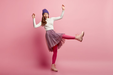 Frightened woman afraids of falling on slippery road, raises hands and legs, wears white jumper and long skirt, winter shoes, stares at camera with surprisement, models over pink background.