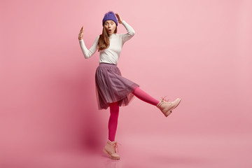 Studio shot of stupefied emotional frighted female model stands sideways, wears blue warm headgear, skirt, bright pink tights, boots, raises legs, overwhelmed by unexpected news. Omg concept