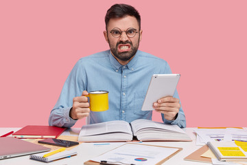 Photo of outraged bearded man dressed in formal shirt, holds cup of drink and touchpad, reads textbook, uses papers for making financial report, isolated over pink background. Work and anger concept