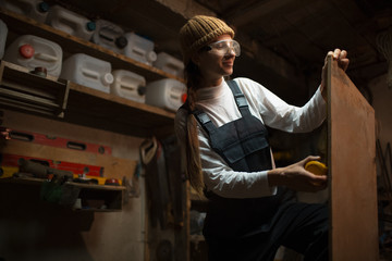 Portrait of smiling young girl carpenters in workshop room