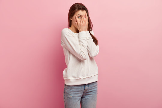 Sideways shot of surprised woman covers face with palms, peeks through fingers, has widely opened eyes, dressed in sweater and jeans, isolated over pink wall with free space for your promotion