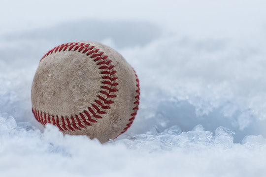 Baseball stuck in snow and ice during winter. Baseball spring training.