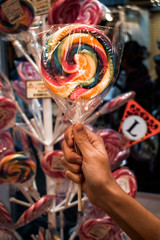 Female hand holding a rainbow colour colored lollipop in front of a holder with lollipops
