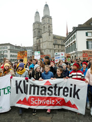 Participants display banners and posters during a demonstration against climate change in Zurich