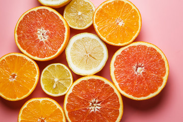 cut in half juicy citruses on a pink background on a tray next to a glass of fresh tasty juice