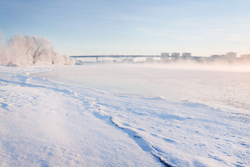Winter landscape in the early morning overlooking the city of Dubna and the bridge over the Volga. Frosty fog obscures the banks of the river. The tops of the trees are covered with hoarfrost.