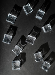 Ice cubes on black stone board. Hard light. Deep shadows. Cold and freshness concept.