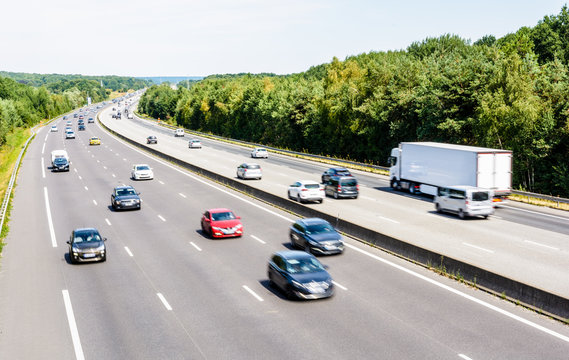Heavy but fluid traffic on the eight-lane A10 highway in France in the direction of Paris by a hot summer day with cars, vans, trailers and semitrailer truck driving.