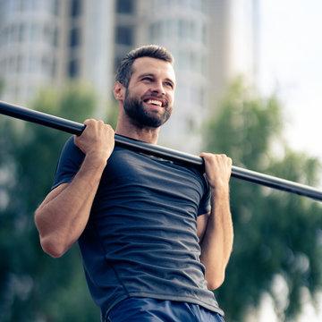 happy man, doing pulling up exercise at horizontal bar