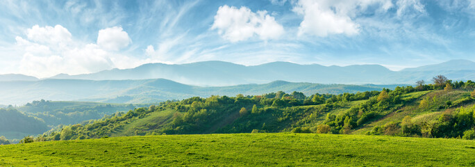 Zelfklevend Fotobehang Cultuur panorama of beautiful countryside of romania. sunny afternoon. wonderful springtime landscape in mountains. grassy field and rolling hills. rural scenery