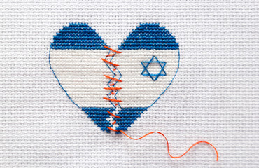 The broken heart of the color of the flag of Israel is sewed with red threads. Heart surgery at Israeli clinics.