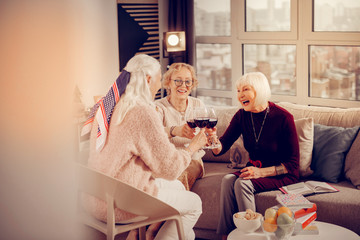 Happy delighted aged women meeting at home
