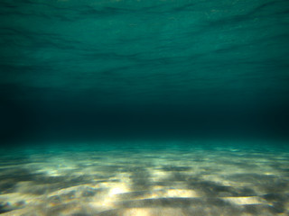 underwater scene with sand and sun reflections