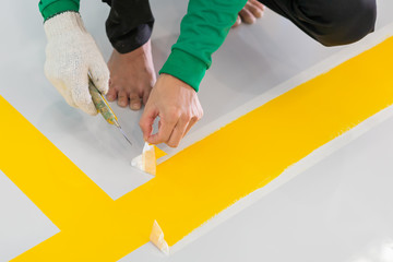 Construction series: Worker removing tape of parking lot stripe