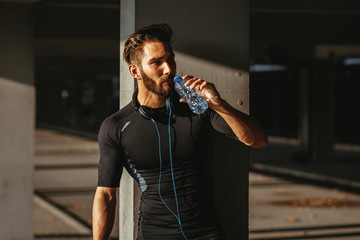 Young man resting and drinking water after jogging