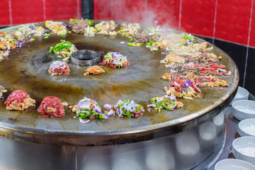 Cooking street food on a large firebox. Frying meat and seafood on the brazier in the street.