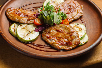 Grilled chicken breast with vegetables on clay plate.