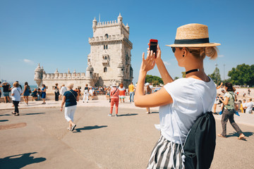 Happy traveler girl in Lisbon near Belem Tower. Tourist woman taking picture of Belem Tower, Portugal