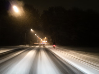Motion Blur: Driving fast on a snowy street with street lights at night