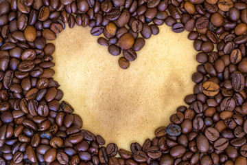 Morning heart. Heart shape made from coffee beans at a vintage paper background