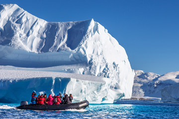 Papiers peints Antarctique Tourists sitting on zodiac boat, exploring huge icebergs driftin