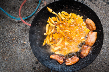 fries and bacon baked on a large metal plate outdoors