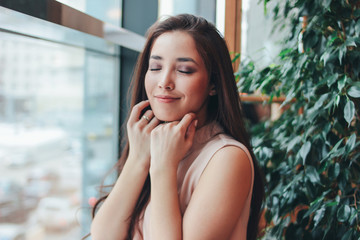 Portrait of beautiful charming romantic brunette smiling asian girl near the window at cafe