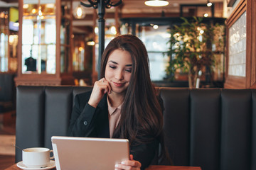 Beautiful charming brunette smiling asian girl with tablet at table in cafe, student, freelancer or young manager